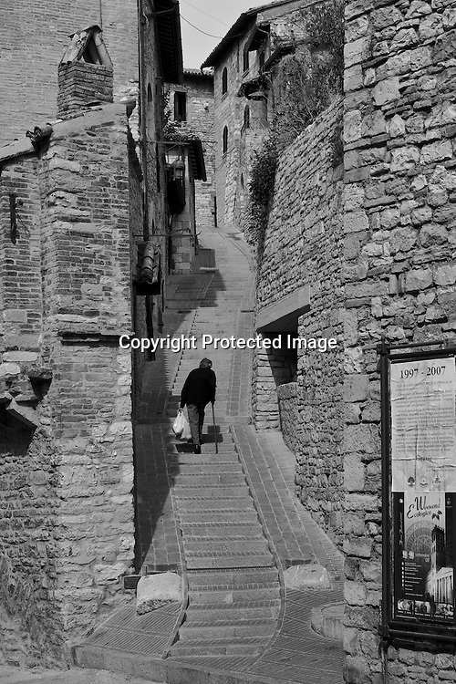 She was returning home from a shopping trip, laboriously climbing the zigzag stairs in the Assisi hillside.