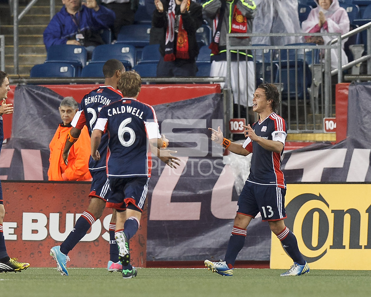 New England Revolution midfielder Ryan Guy (13) celebrates his goal with teammates.  In a Major League Soccer (MLS) match, Real Salt Lake (white) defeated the New England Revolution (blue), 2-1, at Gillette Stadium on May 8, 2013.