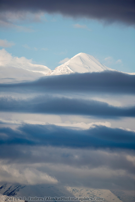 The Summit Of Mt. Denali, North America's Tallest Mountain, Peeks Out Of Layered Clouds, Denali National Park, Alaska.