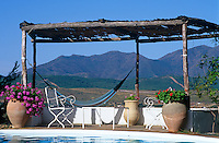 A hammock and garden chairs under a simple wooden pergola overlook the swimming pool with a view of the mountains beyond