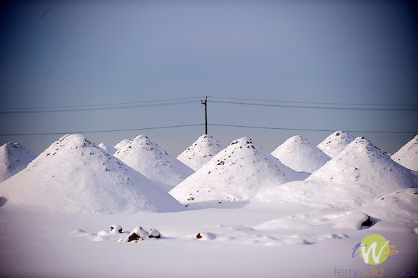 Sand and gravel piles in snow.