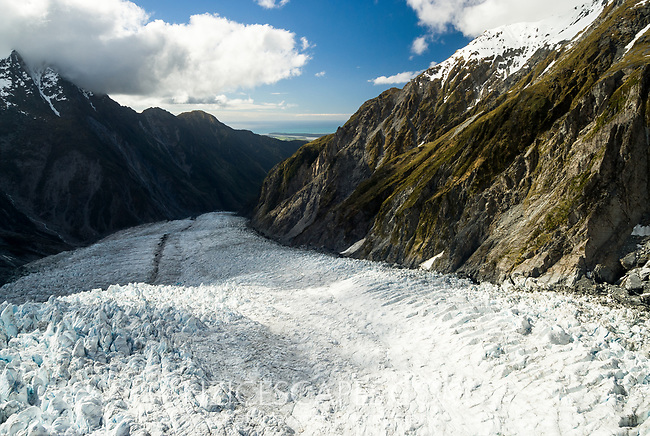 Downstream view into valley across crevasses on Franz Josef Glacier and toward Tasman Sea on horizon, Westland Tai Poutini National Park, West Coast, UNESCO World Heritage Area, New Zealand, NZ