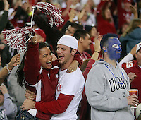 1223101053mf  fiesta0102  1/1/11- Oklahoma fan Dustin Herr (CQ)  hugs his wife Christie Herr (CQ) while celebrating Oklahoma's first touch down of the game as Connecticut fan Cory Whitmore (CQ) looks on in disappointment during the Fiesta Bowl held at the University of Phoenix Stadium in Glendale, Ariz. (Pat Shannahan/ The Arizona Republic)