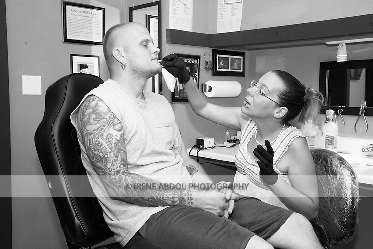 Tracy Baker, an apprentice piercer at a tattoo parlor in Rockland, Maine, dabs alcohol on her mentor's chin in a practice piercing session.