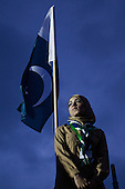 A woman from Pakistan is standing in front of the Pakistani flag at the opening ceremony