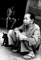 Cam Nghia / Provincia di Quang Tri / Vietnam.<br /> Lo chiamano 'il villaggio maledetto' a causa dell'alta concentrazione di diossina che ha prodotto gravissime conseguenze alla natura e la popolazione.In nove famiglie visitate ci sono undici vittime con malformazioni fisiche e ritardo mentale. Altissima è la percentuale di bambini nati morti..Nella foto, in primo piano, Nguyen Thi Huyen, 73 anni, madre di Le Van Khanh seduto sul letto all'interno della baracca.Le Van Khanh ha 23 anni ed è gravemente affetto dalla sindrome da diossina. I suoi fratelli ed il padre sono morti per lo stesso motivo nel corso degli anni.Le Van Khanh non sente, non parla e non può camminare.Le condizioni di vita sono poverissime. Senza medicine, isolati nel folto della foresta, si cibano dei frutti della terra.<br /> Foto Livio Senigalliesi.<br /> Cam Nghia / Quang Tri / Vietnam<br /> Conseguences of the war in Vietnam after 40 years.Nguyen Thi Huyen (73) mother of Le Van Khanh (23) affected by dioxine sindrome.<br /> Cam Nghia is called 'village of damned' becouse high percent of children born deformed or physically and mentally handicapped.<br /> Photo Livio Senigalliesi