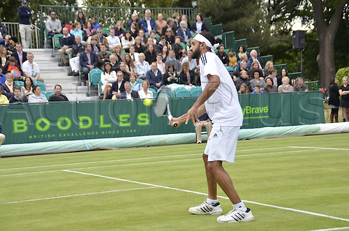 22.06.2013. Stoke park, Slouogh, berkshire, England. The Boodles Challenge mens doubles finals. Jamie Delgado of Great Britain and his American partner James Cerrentani versus the pairing of Adil Shamasolin and Rameez Junaid. Rameez Junaid returns at the net