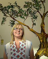 NWA Democrat-Gazette/BEN GOFF @NWABENGOFF<br /> Gina Phillips, a painter and textile artist based in New Orleans, poses for a photo with her piece 'A Sentimental Tree Reminisces' Friday, Aug. 28, 2015 during an opening reception and tour of her new exhibit at 21C Museum Hotel in Bentonville,