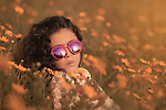 A girl with glasses lies in flowers field. Photo by Sanad Ltefa