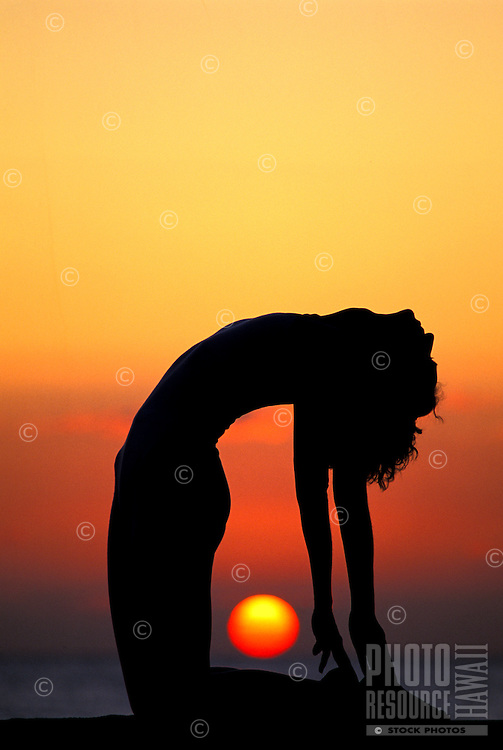 Woman in yoga posture at sunset
