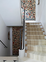 The staircase has a metal balustrade and neutral carpet runner. Decorative crewel pattern panels hang on the walls.