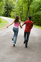 Young couple skipping down country road holding hands
