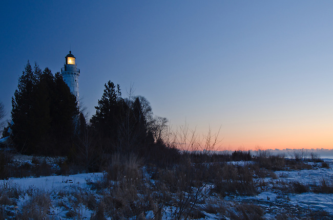 Cana Island Lighthouse shines into the pre-dawn light in Door County, Wisconsin.  The light turns off automatically just before sunrise each day.