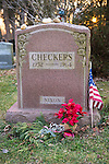 "Wantagh, New York, USA. February 5, 2017.  CHECKERS (1952 - 1964), President Richard Nixon's pet dog, is buried in Bide-a-Wee Pet Memorial Park cemetery. The red granite gravestone is inscribed with Checkers' name, year of birth and death, and ""NIXON"" - and has a small American Flag at its side."
