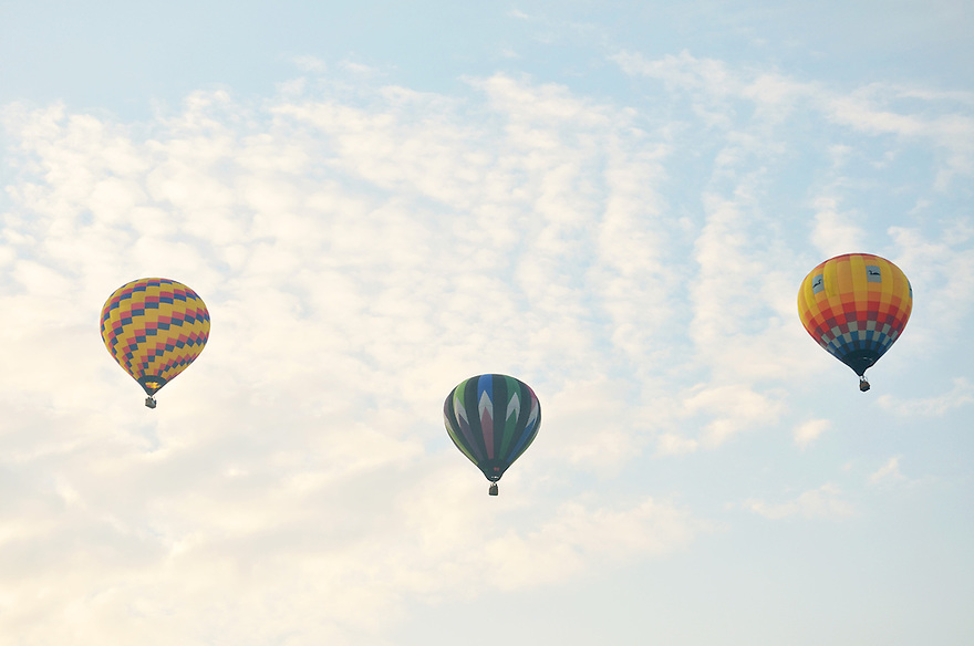 A trio of hot air balloons assume formation in the early morning sky.