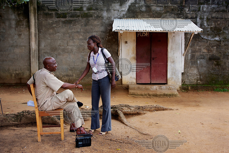 Baindu Koroma, a paralegal who works for Timap for Justice, greeting the second in command at Bo Prison prison whio is seated on a wooden chair listening to a radio outside the entrance gate to the facility. <br /> Koroma's work includes making regular visits to police stations, the prison, and the courts to monitor whether people are being afforded their lawful rights, for example, the right to bail, legal representation, detention without charge, etc, and if not to advocate on their behalf.