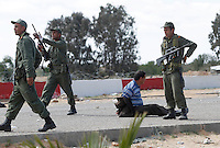 Tunisian military fire into the air to disperese a crowd and detain people suspected of taking advantage of refugees. Tens of thousands of people, mainly Egyptian workers, fled unrest in Libya and crossed the border into Tunisia. Some slept in the open for several days before being processed.  At the same time forces loyal to Col. Gaddafi fought opposition forces in various parts of the country.