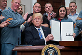 US President Donald J. Trump (C) signs a presidential proclamation on steel tariffs, beside workers in the Roosevelt Room of the White House in Washington, DC, USA, 08 March 2018. President Trump is imposing tariffs on steel and aluminum imports. A decision to impose the tariffs on Canada or Mexico will not be decided until negotiations on the North American Free Trade Agreement (NAFTA).<br /> Credit: Michael Reynolds / Pool via CNP