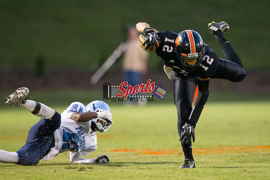 Nathan Clark (12) of the Northwest Cabarrus Trojans flies through the air after being tripped up by JT Sanders (21) of the West Rowan Falcons at Trojan Stadium September 19, 2014, in Concord, North Carolina.  The Falcons defeated the Trojans 13-0.  (Brian Westerholt/Special to the Tribune)