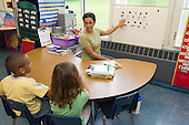 MR / Schenectady, NY. Zoller Elementary School (urban public school). Kindergarten classroom. Paraprofessional (Puerto Rican American) teaches Spanish-language lesson to bilingual students. Left: boy, 6, African American /  Puerto-Rican American; Right: girl, 5; both are native Spanish speakers. MR: Pac1, Car38, Cas12. ID: AM-gKw. © Ellen B. Senisi.