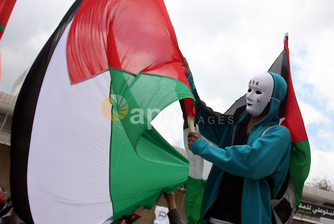 A masked Palestinian protester holds his national flag as he commemorates Land Day in Qalandia which lies between Jerusalem and the West Bank city of Ramallah on March 30, 2012. Land Day marks the annual event that commemorates the deaths of six Arab Israeli protesters at the hands of Israeli forces during mass demonstrations in 1976 against plans to confiscate Arab land in northern Israel. Photo by Issam Rimawi