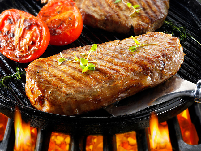 Sirloin beef steaks & tomaotoes being pan fried on a bbq. Meat food photos, pictures & images.