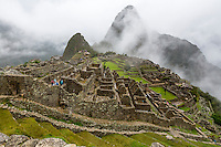 Peru, Machu Picchu.  Early Morning Clouds Lifting.  Huayna Picchu in Background.