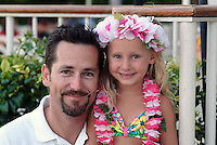 Portrait of a father with his daughter wearing flower leis and hula skirt while on vacation in Hawaii