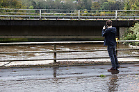 Pictured: A man takes a picture of the river Neath which has uproached the A465 dual carriageway at Aberdulais Falls in south Wales, UK. Saturday 13 October 2018<br /> Re: Flooding caused by Storm Callum in Aberdulais near Neath, south Wales, UK.
