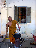 Buddhist Monk in his Monastery preparing his tea with a laptop and his cigarettes on the table, Battambang, Cambodia