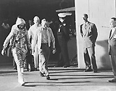 View of astronaut John H. Glenn Jr., Dr. William Douglas, Astronauts Flight Surgeon, and equipment specialist Joe Schmitt leaving Operations and Checkout Building at Cape Canaveral, Florida prior to Mercury-Atlas 6 (MA-6) mission on February 20, 1962. Glenn is in his pressure suit and is carrying the portable ventilation unit.Credit: NASA via CNP