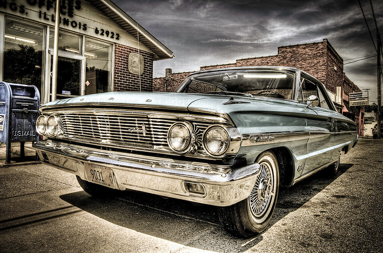 A 1960's Ford Galaxy car with chrome fender parked on street in US