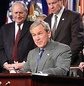 United States President George W. Bush signs H.R. 1588, the National Defense Authorization Act of Fiscal Year 2004 at the Pentagon in Arlington, Virginia on November 24, 2003. United States Senator Carl Levin (Democrat from Michigan), the ranking member of the Senate Armed Services Committee, left, and United States Representative Tom Davis (Republican of Virginia), right, look on.<br /> Credit: Ron Sachs / CNP