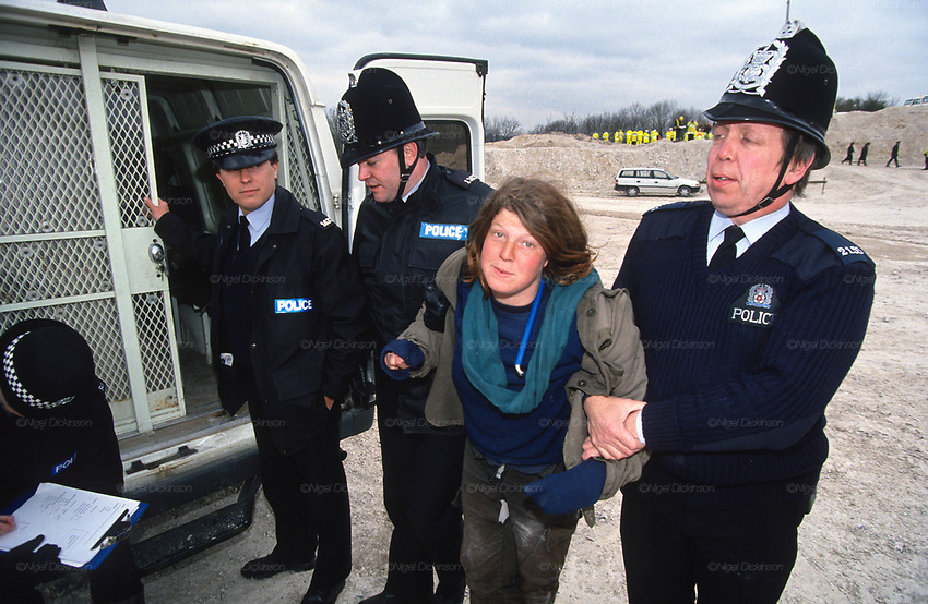 Rebecca Lush arrested by police in the cutting. Road Protest actions at Twyford Down, near the Donga pathways, outside Winchester, against the M3 road extension. 1993<br /> <br /> The British Road Protesters movement began in the early 1990s when the Donga tribe squatted Twyford Down to save this beautiful site, a site of scientific interest SSI from the Ministry of transport's road building programme which threatened to destroy the landscape. The Dongas was the name of the ancient walkways, the paths trodden in the middle ages by people walking down to Winchester. A small tribe were joined by people of all walks of life who came to Twyford Down to defend it. A long hard battle over several years ended in the 'cutting' a new motorway built through this ancient monument and destroying it. <br /> <br /> The Road Protest movement in Britain continued for many years and more battles were fought in London against the MII both at Wanstead then in Leytonstone, and subsequently at Newbury, and in Sussex. the protesters were very inventive in their use of non violent peaceful direct action. They barricaded themselves into squats, made tree houses, tunnels and have huge demonstrations against the bailliffs, police and security who tried to force their way through the defences of this alternative environmental popular movement. Many of the roads were built eventually and many sites of great beauty lost, but the government had to stand down from its road building policy and eventually the programme was halted. the protests cost the government billions. Out of that movement grew many environmental NGOs who have to this day kept fighting for ecological and sustainable environmental solutions rather than following the cult of the car, petrol and roadbuilding..