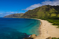 Makua Beach and Bay along the west coast of O'ahu, seen from above on a sunny day.