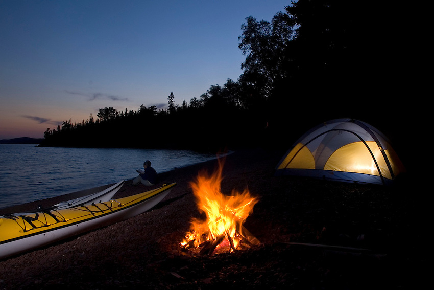 A campfire burns and a tent is lit at a sea kayaker campsite at Fish Cove on the Keweenaw Peninsula near Copper Harbor Michigan.