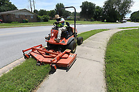 NWA Democrat-Gazette/J.T. WAMPLER Henry Hernandez, an employee of Springdale Street Department, mows in a city right-of way Tuesday June 11, 2019.