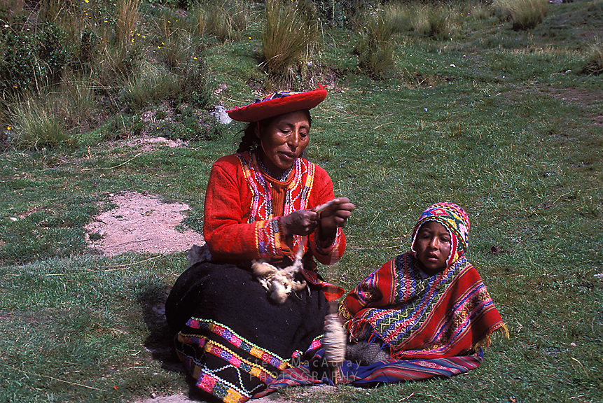Mother and young child in traditional clothing resting and spinning wool on a handspinner tool, Tambo Machay, Peru