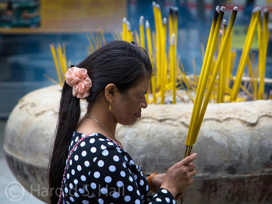 A Hindu lady prays and burns incense for her family at a shrine in Hong Kong, China.