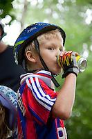 Polish boy age 8 enjoying a soda after a bicycle ride wearing a helmet. Paderewski Park Rzeczyca Central Poland