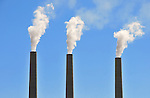 Three chimneys from coal-fired powerplant in Page, Arizona with blue sky background.