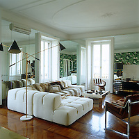 A vintage Arredoluce Triennale floor lamp illuminates the elegant white Patrica Urquioia sofa in the living room