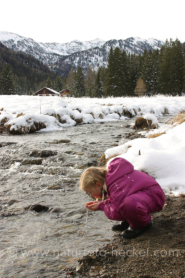 Mädchen trinkt im Winter kristallklares Gebirgswasser direkt aus dem Bach