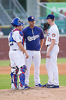 Chattanooga Lookouts pitching coach Scott Radinsky (center) has a meeting on the mound with starting pitcher Chris Reed (29) and catcher Chris O'Brien (27) during the game against the Montgomery Biscuits at AT&T Field on July 24, 2014 in Chattanooga, Tennessee.  The Biscuits defeated the Lookouts 6-4. (Brian Westerholt/Four Seam Images)