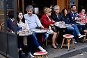 Paris, France. 09.05.2015. Tourists at a pavement cafe, Place du Tertre, Montmartre, Paris, France. Photograph © Jane Hobson.