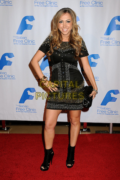 DIANA MADISON.33rd Annual Saban Free Clinic Dinner Gala held at the Beverly Hilton Hotel, Beverly Hills, California, USA..November 23rd, 2009.full length black dress studs studded ankle boots open toe clutch bag hand on hip.CAP/ADM/BP.©Byron Purvis/AdMedia/Capital Pictures.
