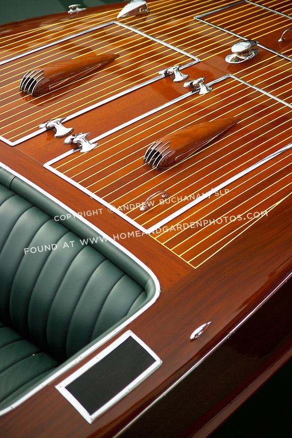 Mahogany wood, chrome, and deep green leather gleam in this detail shot of a classic wooden boat