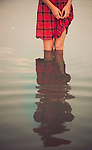 Young woman wearing a red dress standing alone in a pond with reflection
