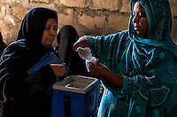 A Pakistani lady health worker collects oral polio vaccine, during 'Anti-polio campaign' in Karachi, Pakistan on Jan. 19, 2015