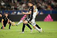 CARSON, CA - SEPTEMBER 15: Sebastian Lletget #17 of the Los Angeles Galaxy reaches the ball before Graham Smith #16 of Sporting Kansas City during a game between Sporting Kansas City and Los Angeles Galaxy at Dignity Health Sports Complex on September 15, 2019 in Carson, California.